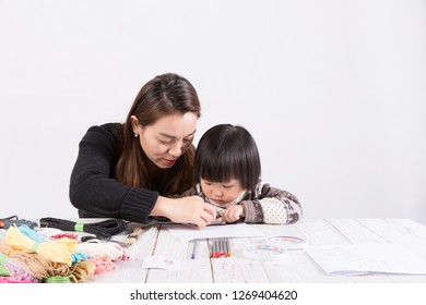 Little girl and mother use color rope to make handmade art