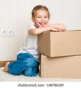 Little girl moving into new house, siting near box