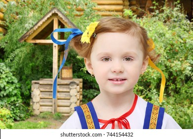 Little girl in national russian costume poses near log well with bucket among green bushes, collage, focus on child