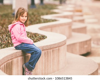 Little Girl in natural sunlight looking at the camera with a film look desaturated tone