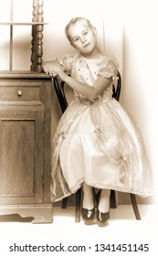 Little girl near the beautiful old bedside table. Photo in vintage style.