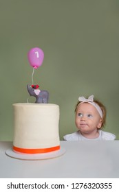 Little girl near birthday cake. One year old girl celebrating her first birthday. Birthday Stollen pie The concept of a children's holiday. Confectionery advertisment background.