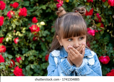 Little girl near a rose bush. Sign language. You can't say, you must be silent. Ban. Tabu. Communication