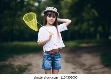 little girl with a net catching butterflies