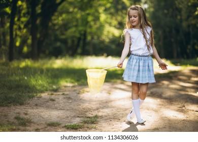 Little girl with net catching butterflies