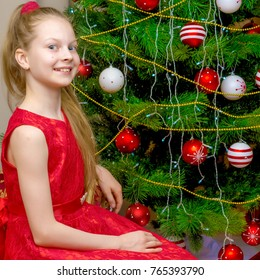 A little girl at the New Year's, Christmas tree.The concept of a holiday, happiness, a child, family well-being, Happy childhood.