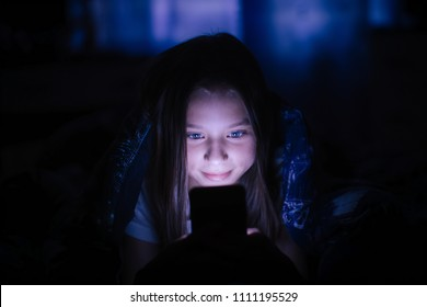 Little girl at night under a blanket looking at the smartphone.