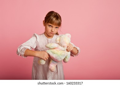 Little girl in a nightgown abusing her teddy bear