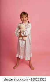 Little girl in a nightgown with a teddy bear on a pink background