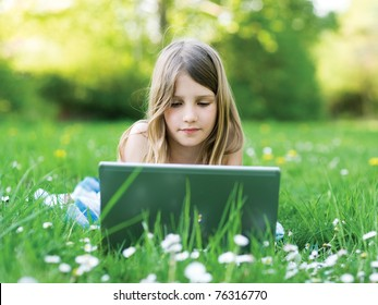 LIttle girl with notebook computer on green meadow