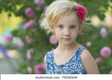 The little girl on a background of roses