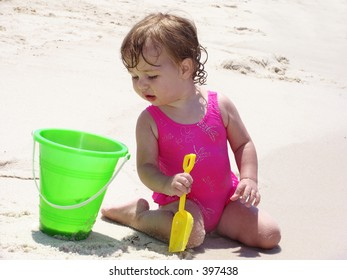 Little girl on the beach peering curiously into a bucket