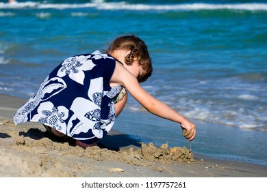Little girl on the beach of the sea is building a sand castle