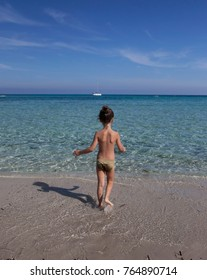 Little girl on the beach on the shore of the transparent sea