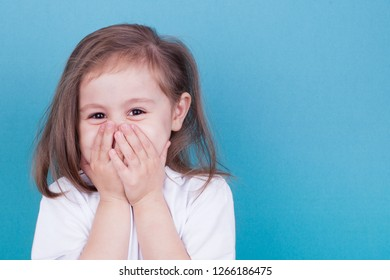 Little girl on a blue background laughs covering her face with her hands