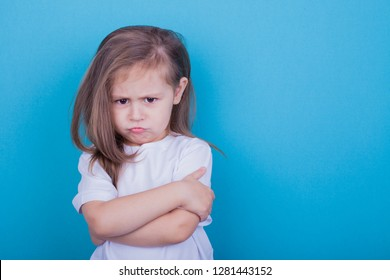 The little girl on a blue background was offended by folding her arms and frowning eyebrows