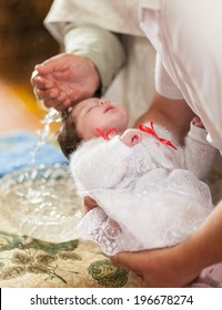Little girl on ceremony of child christening in church
