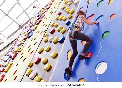 Little girl on climbing wall in entertainment center.