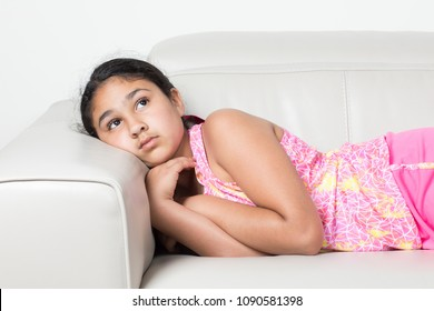 Little Girl On a Couch With a Thoughtful Expression