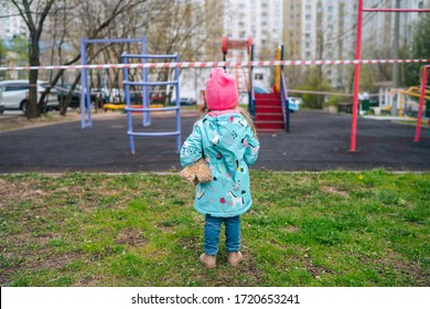little girl on an empty closed playground closed quarantine of the corona virus, isolation, covid 19