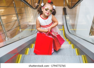 little girl on the escalator in the mall with purchases