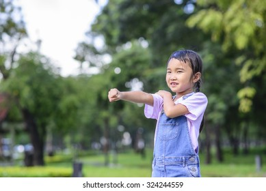 Little girl on exercise pose; Beautiful green bokeh background; Green park