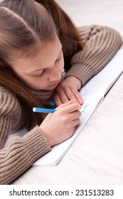 little girl on the floor writing concentrated on her exercise book with a coloured felt-tip pen