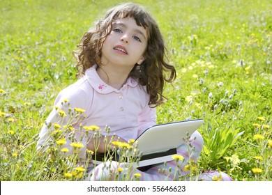 little girl on garden meadow notebook computer homework outdoors
