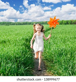 little girl on grass in summer day holds windmill in hand