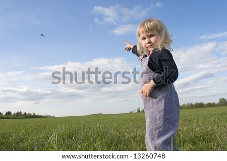 little girl on green grass meadow pointing to the plane in the sky by her finger