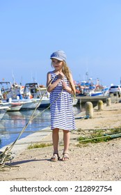 Little girl on the harbor holding a rope
