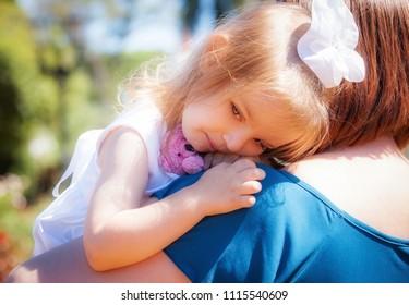 little girl on her mother's shoulder in the park
