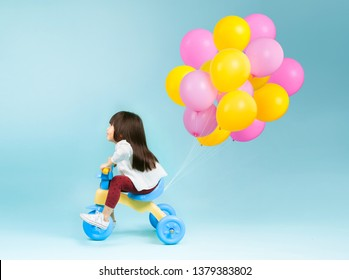 Little girl on a kids tricycle with colorful balloons behind on plain background.