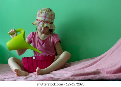 little girl on pink rug with green background holding the green watering can and pink flower pot wearink a hat and pink shirt