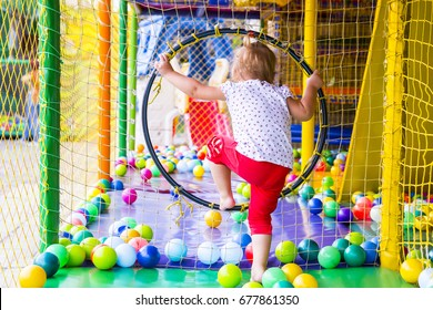 Little girl on the playground with colored plastic balls