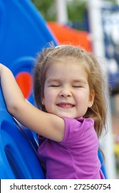 little girl on the playground. Happy smiling child playing on outdoor.