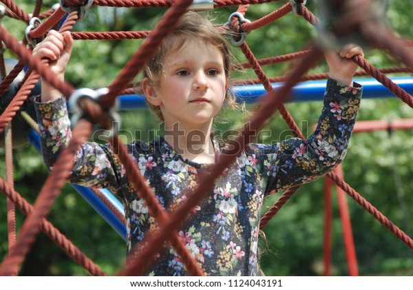 The little girl on the playground surrounded by ropes. The playground is located in the park between green trees.
