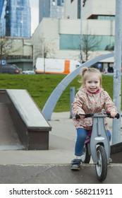 Little girl on pushbike. Having fun at skateboarding ramp park
