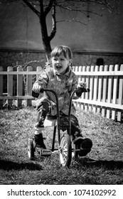 Little girl on a retro tricycle. Black and white photo in retro style