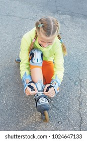 Little girl on roller skates in park. Happy girl. Child and sports. Active childhood.