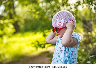 A little girl on a summer green background trying on sunglasses