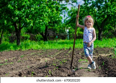 Little girl on a sunny day in the garden with a hoe