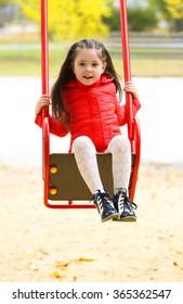 Little girl on swing in city park