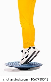 Little girl in on the tips of toes position staing on balance board. Proprioception exercises. Photo on white background
