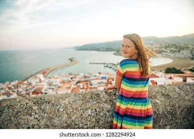 Little girl on the top of Peniscola, admiring amazing summer sunset, travel with children, wearing colorful dress