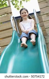 Little girl on top of slippery slide, portrait