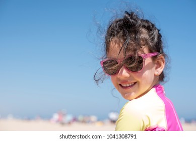 Little girl on vacation posing on the beach