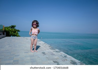Little girl on a vacation at the sea. Asian baby girl is relaxing near by the sea.