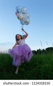 Little girl on a walk in a field with balloons, summer evening