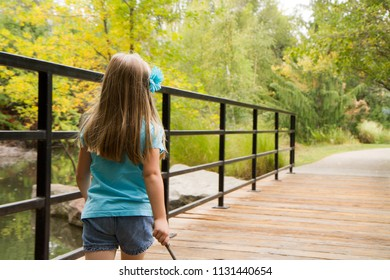 Little girl on a wooden bridge in the woods walking down her path of exploration